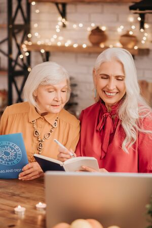 Active seniors. Two grey-haired pleasant cute ladies looking interested while studying together Foto de archivo