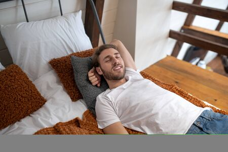 Sleeping well. A handsome young man sleeping on pillows in the bed Banco de Imagens