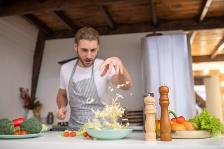 Cooking as a magic. A professional cook putting cabbage into a salad