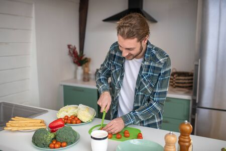 Vegeterian lifestyle. A man cutting vegetables for making a salad