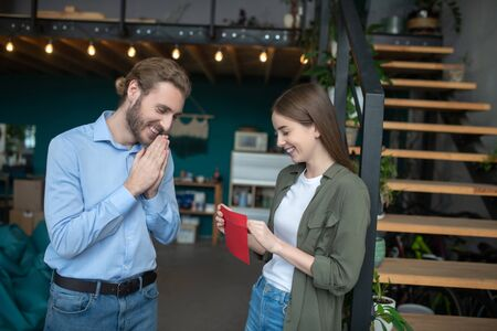 Thrilling waiting. A smiling woman and man opening an envelope Stock Photo