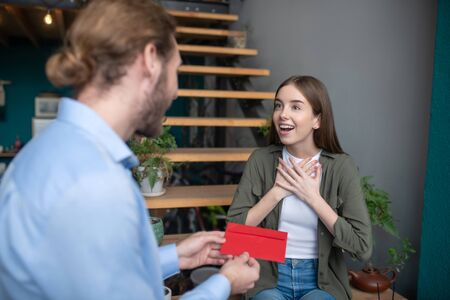 Surprising letter. A man giving a red envelope to the admired woman