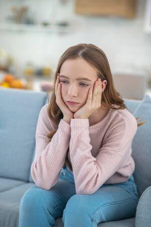 Âge difficile. Fille triste pensive assise sur le canapé, soutenant sa tête avec ses mains regardant vers le bas, pensant.