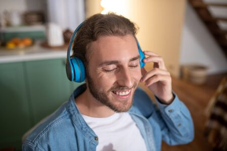 Music lover. A smiling man wearing blue earphones while listening to music