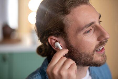 Comfortable earphones. A handsome long-haired man wearing white wireless earphones 免版税图像