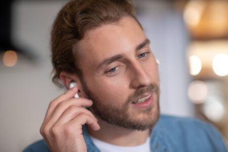 Enjoying music. A handsome long-haired man wearing white wireless earphones