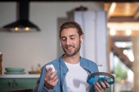 Earphones that fit you. A young man testing different types of earphones