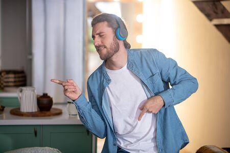 Enjoying music. An emotional young man dancing while listening favourite music