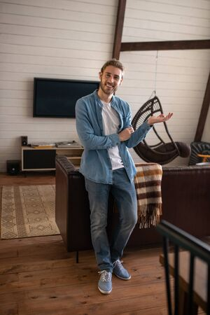 Having a big appartment. A smiling handsome man standing in his livingroom