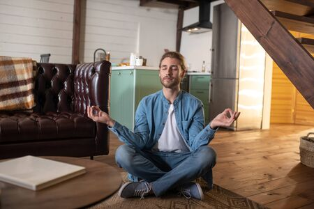 Meditating easily. A concentrated young man practicing meditation at home 스톡 콘텐츠