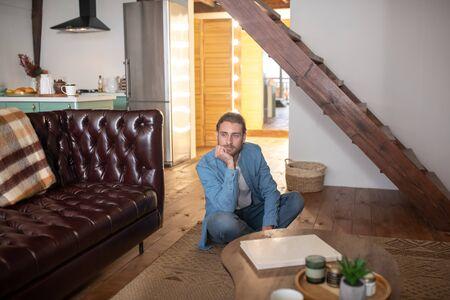 Stando a casa. Un uomo annoiato seduto per terra nel suo appartamento Archivio Fotografico