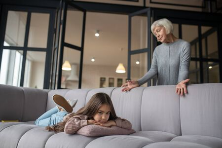 Little misunderstanding. Little sad girl lying on her stomach on the couch and grandmother standing behind the sofa and looking at the granddaughter with a misunderstanding.