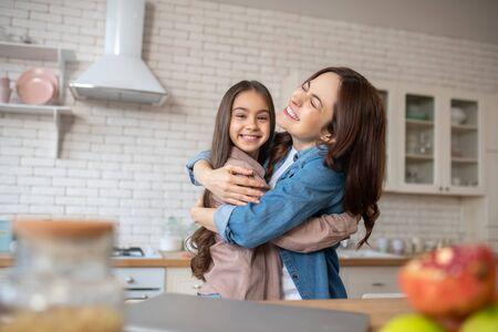 Las mamás aman. Hermosa joven madre con una pequeña hija bonita, abrazado de pie en la cocina, feliz. Foto de archivo