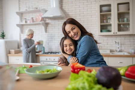 Moms care. Mom and daughter hugging sitting at the kitchen table beautiful and happy, and grandmother standing at the stove. Stockfoto