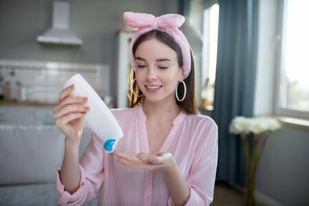 Body Lotion. Lächelndes hübsches Mädchen in einem rosa Stirnband, das Lotion gießt Standard-Bild