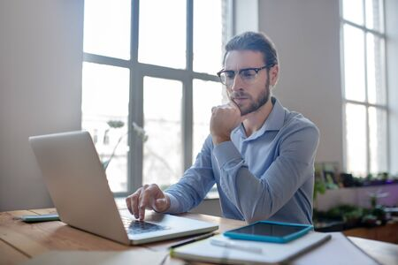 Job analysis. Young smart man with glasses and a light blue shirt looking at the laptop screen while holding his hand above the keyboard, sitting at the table.