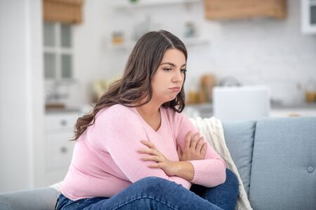 Bad mood. Full-figured young woman in a pink shirt feeling depressed