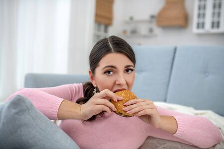 Burger. Full-figured young woman in a pink shirt eating a burger