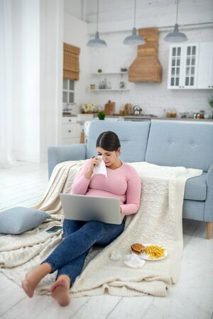Feeling bad. Full-figured young woman in a pink shirt sitting with a laptop and crying
