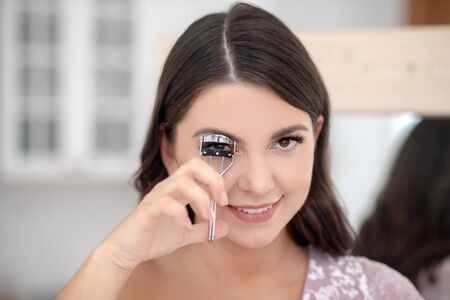 Eyelashes. Young pretty full-figured smiling woman curling her eyelashes