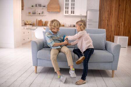 Zu Hause. Kinder streiten, nehmen Tabletten voneinander