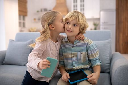 At home. Children sitting on sofa, holding gadgets, girl kissing and embracing boy, both are happy