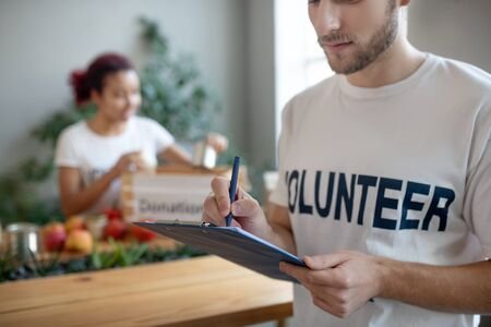 Summing up work. Young volunteer with beard with blue folder and pen in his hands, standing in room and writing, attentive busy, the girl behind is packing products. Stock Photo