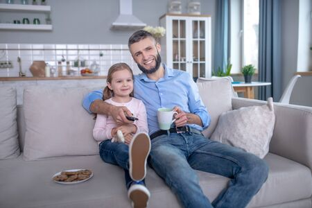 Great day. Young bearded dad with a cup and a remote control in his hands a little long-haired daughter sitting together on the couch, in a good mood. Stock fotó