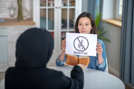 Gluten intolerance. A woman refusing to eat bread containing gluten