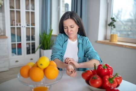 Allergy causing products. A woman itching her hand after eating allergens Stockfoto