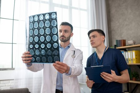 MRI. Two young doctors looking serious while analyzing MRI results Stock Photo