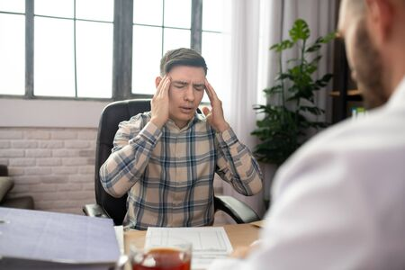 Headache. Patient in checkered shirt touching his head and complaining to the doctor Stock Photo