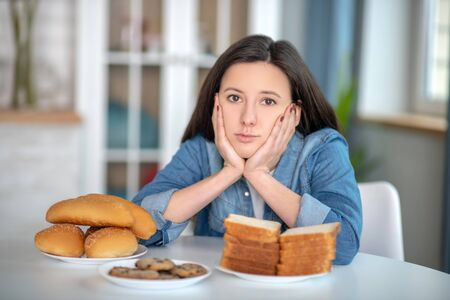 Carbs consumption. A woman looking at the plates with buns and bread
