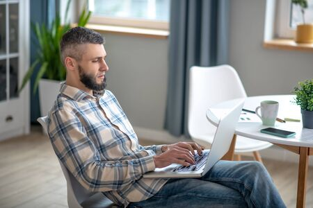 Freelancer. Young serious man sitting on a chair near the table, holding a laptop in his hands, typesetting.