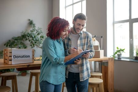 Work moment. Young man in a plaid shirt and a girl with bright hair writing in a work notebook standing in the office, smiling.