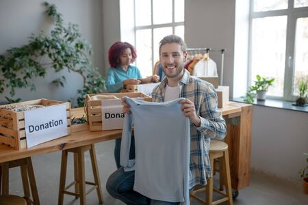 Clothes sorting process. Young smiling man sitting on a chair holding in his hands and showing a white sweater, a young girl folding clothes at the table.