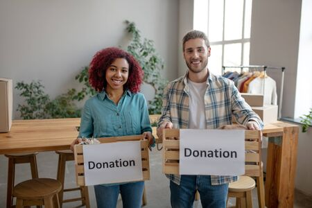 Good purposes. Young girl with burgundy curly hair and a man with a beard, standing in the room holding boxes with clothes for humanitarian aid, happy smiling.