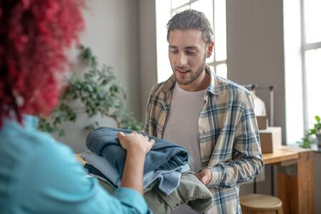 Clothing packaging. Young handsome man in a plaid shirt and a girl standing and passing clothes to each other.