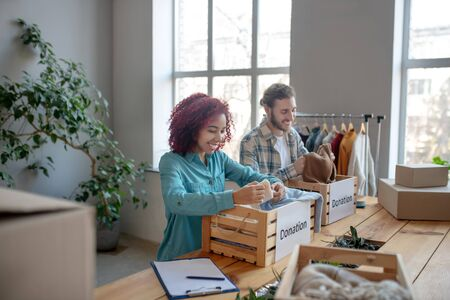 Clothing calibration. Young adult man and girl sorting clothes in wooden boxes on the table, smiling and joyful. Reklamní fotografie