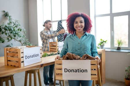 Donations of clothes. Young smiling girl standing and holding a box with clothes for donation, a man standing at the table.
