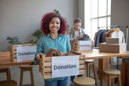 Good deed. Happy young girl standing with a box of clothes for a donation, a young man standing at a table folding things into boxes.
