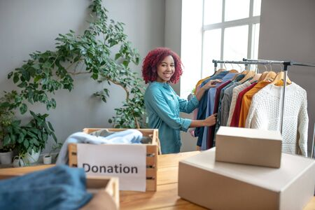Help people and benefit. Young girl with curly hair sorting and folding clothes into charity boxes, rejoicing benefiting and helping people.