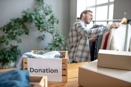 Donation box. Wooden donation box filled with clothes standing on a table among other boxes, a man at a rack with clothes sorting. Banque d'images