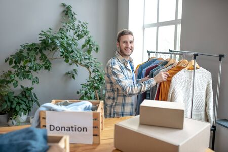Work in social organization. Young joyful man working in a social organization standing at the counter with clothes and sorting it for charity.
