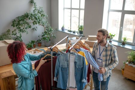 Hanging clothes. Young girl with curly hair and a man with a badge standing near a rack with clothes and sorting clothes on trempels for a charity sale, smiling cheerful. Reklamní fotografie