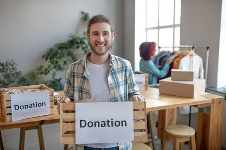 Clothing for donation. Young smiling man standing in a room with a drawer of clothes for a donation, a girl with burgundy hair standing in the back of the room. Reklamní fotografie