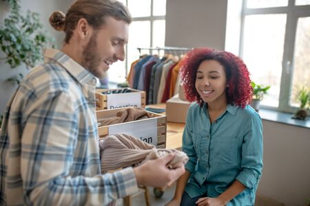 Communication at work. Joyful man in a plaid shirt with a sweater in his hands and a young sitting girl looking at a sweater, they are smiling and talking. Reklamní fotografie