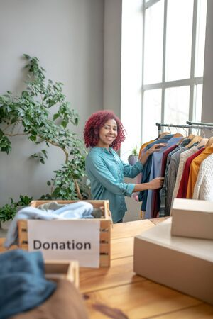 Charity work. Young joyful girl working in a charity, standing in the room and looking at clothes hanging on trempels for a donation. Reklamní fotografie