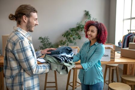 Clothing for needy. Young girl and man packing clothes to help those in need, standing in a large bright room, in a good mood. Reklamní fotografie