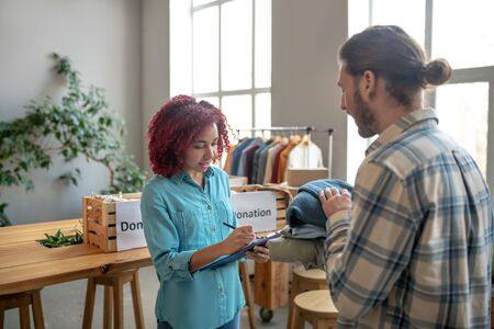 Accounting for work done. Young attentive girl with burgundy hair standing and writing in a notebook, and next to him a man with folded clothes in his hands.
